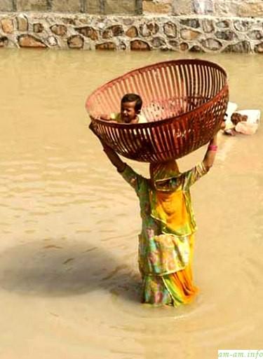 Индийская мама переходит реку вброд - так же, как это делали много раз до нее…
